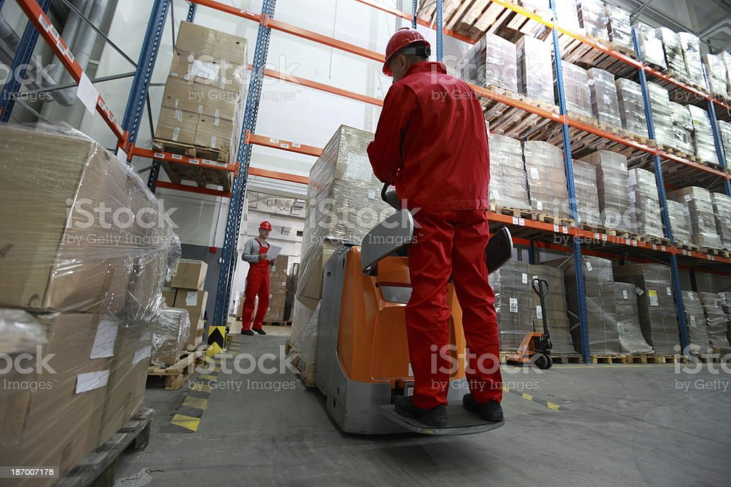 Goods delivery , workers working in storehouse with forklift loader stock photo