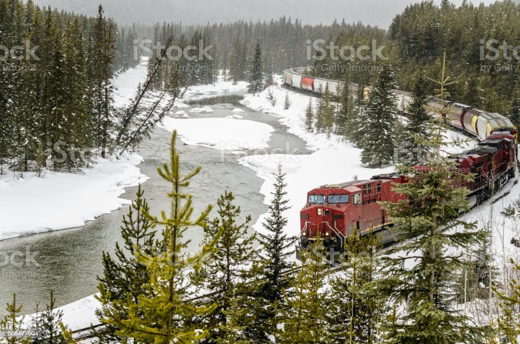 Goods Train in a Mountain Landscape during a Snowstrom stock photo