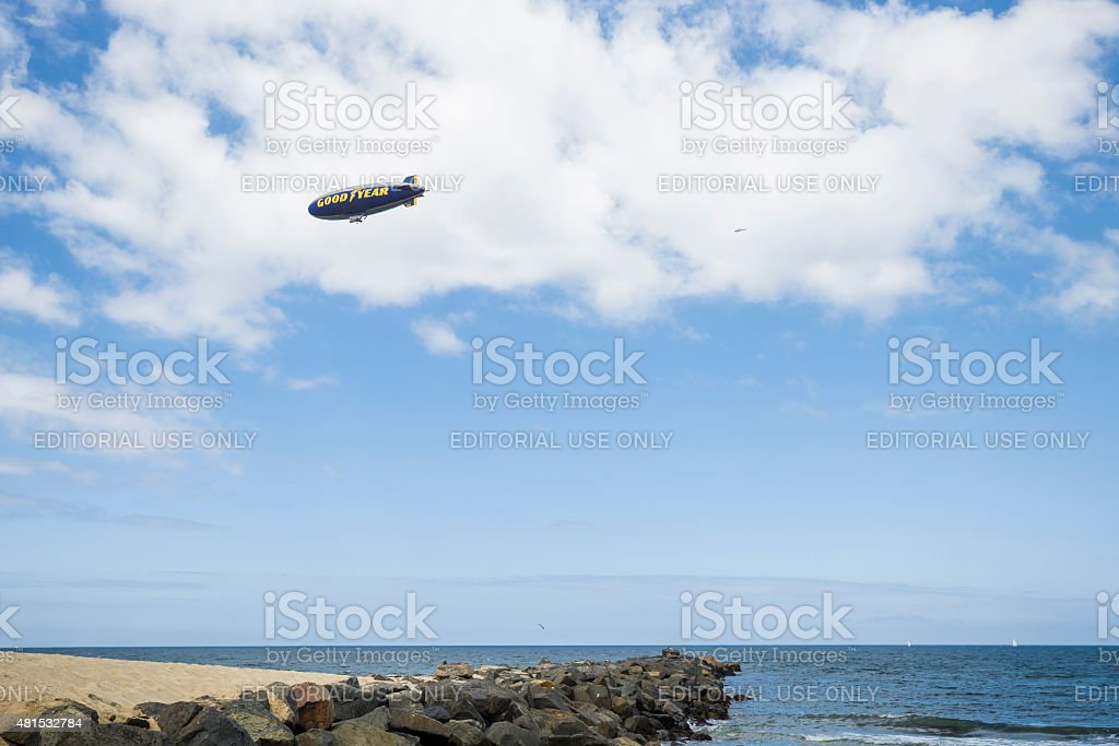 Goodyear Blimp Flying Over Rock Pacific Ocean Shore, Horizontal stock photo
