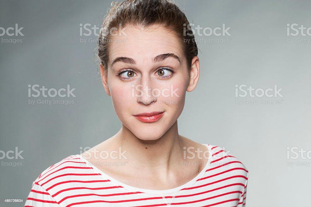 goofy 20s girl having fun with a cross-eye funny face stock photo