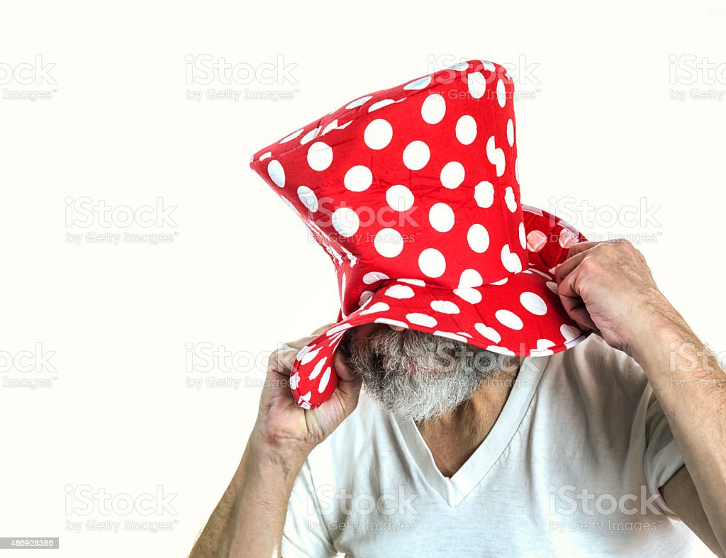 Goofy Clown Man Pulling Polka Dot Clown Hat Over Head stock photo