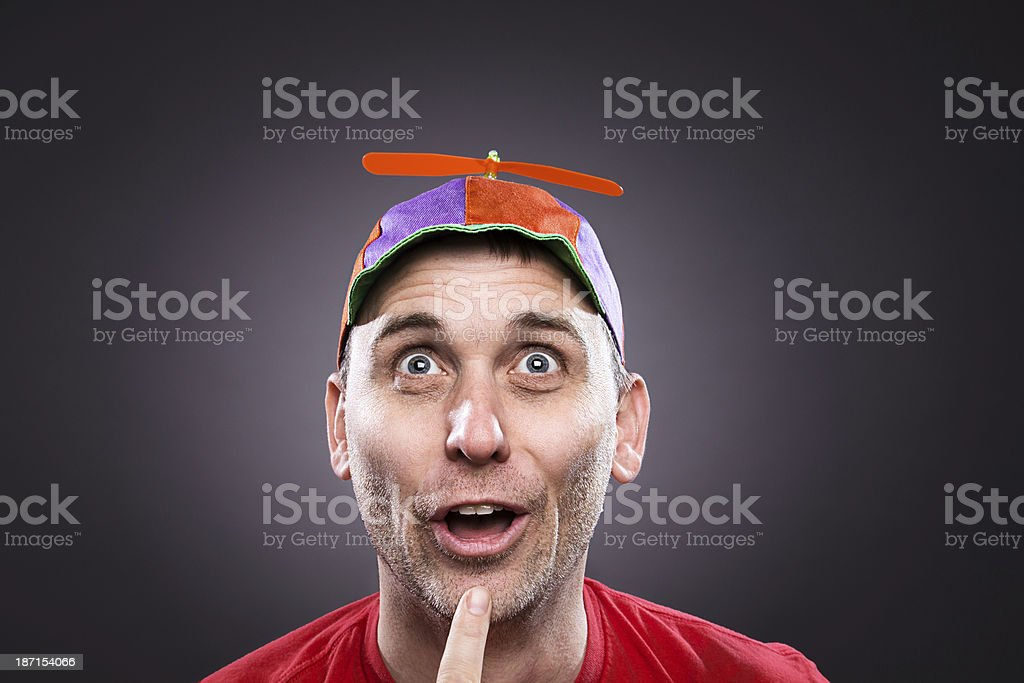 Goofy man wearing a propeller beanie thinking stock photo