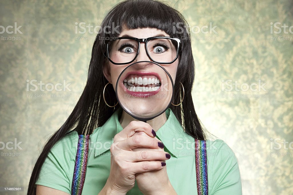Goofy Nerd Woman Smiling With Magnigying Glass Over Teeth royalty-free stock photo