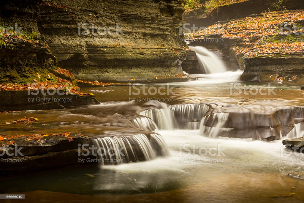 Gorge waterfall with leaves and soft cascades stock photo