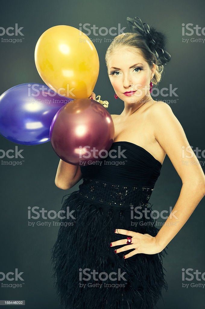 Gorgeous blond young woman in evening dress with baloons, posing stock photo