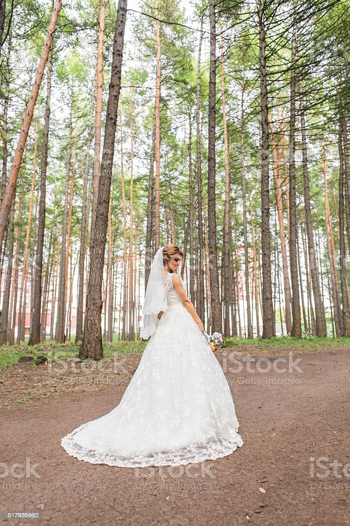 Gorgeous  Blonde bride with bouquet outdoor, posing stock photo
