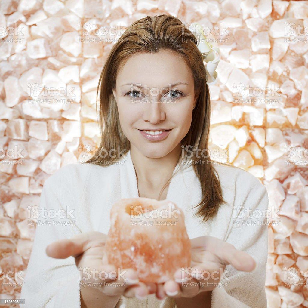 Gorgeous blonde woman holding natural rock salt. stock photo
