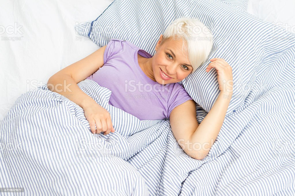Gorgeous blonde woman posing on the bed while smiling royalty-free stock photo