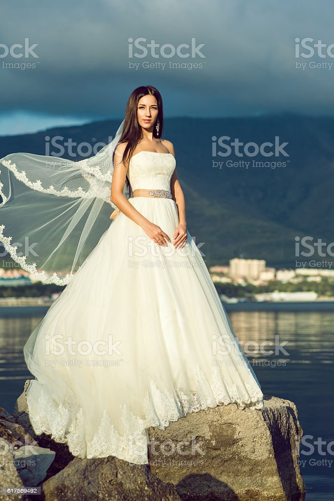 Gorgeous bride in luxurious wedding dress at the seaside stock photo
