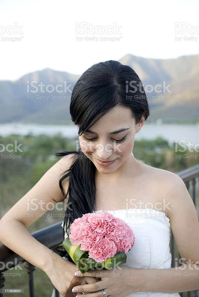 gorgeous bride looking at her bouquet royalty-free stock photo