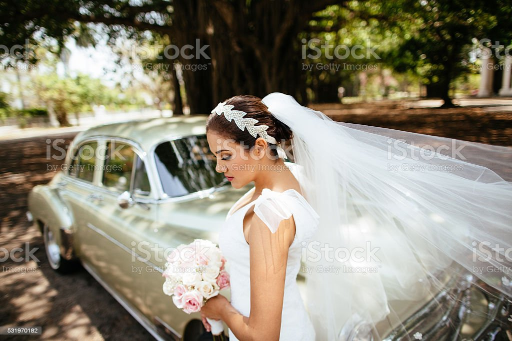 Gorgeous bride standing in front of classic car stock photo