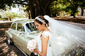 Gorgeous bride standing in front of classic car