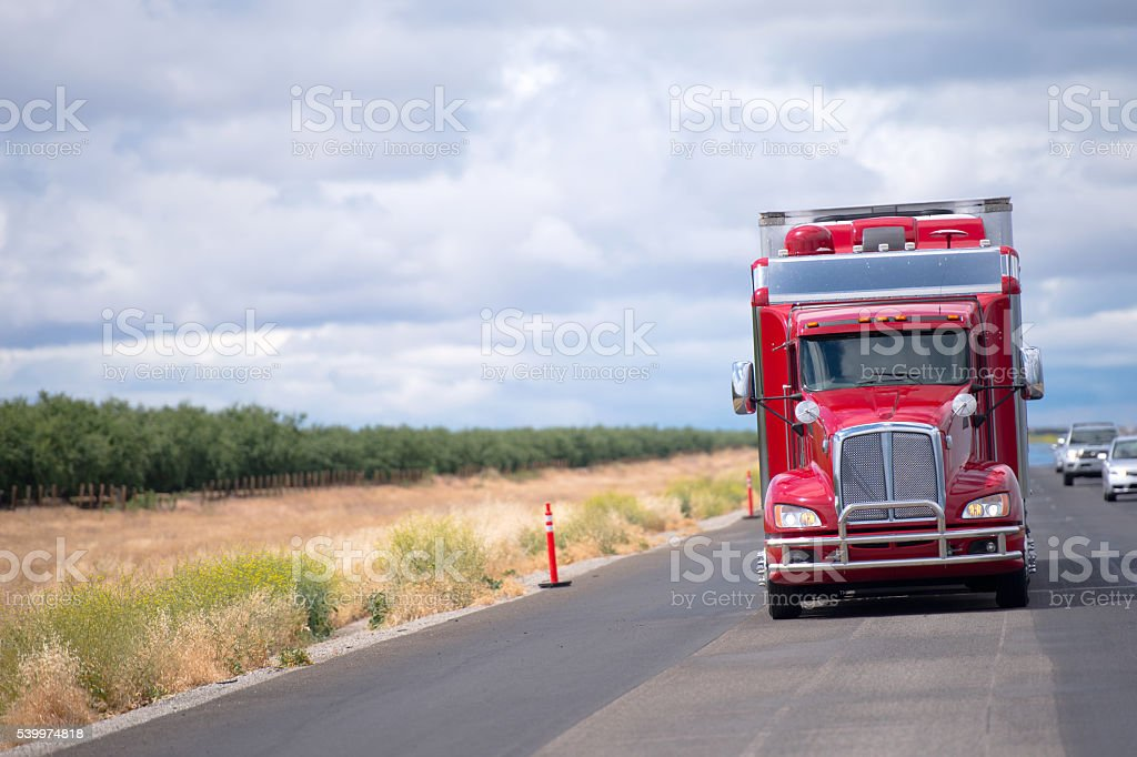 Gorgeous custom tuned red semi truck rig with reefer trailer stock photo