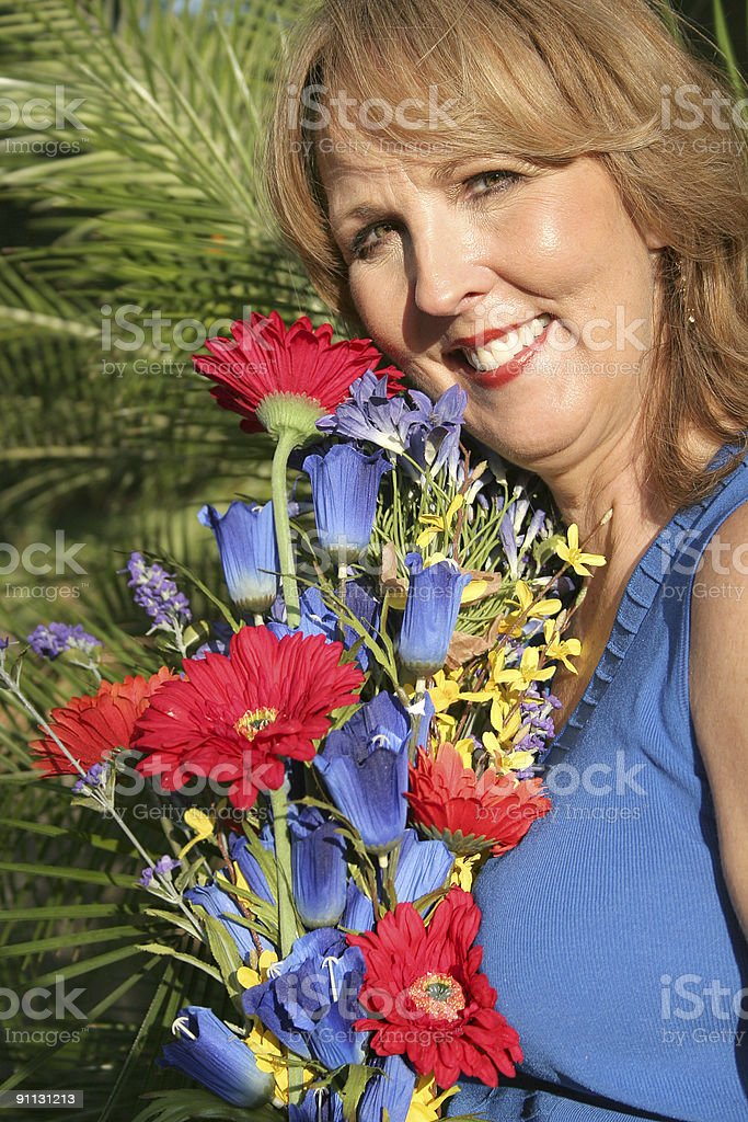 gorgeous fifty year old woman with flowers vertical royalty-free stock photo