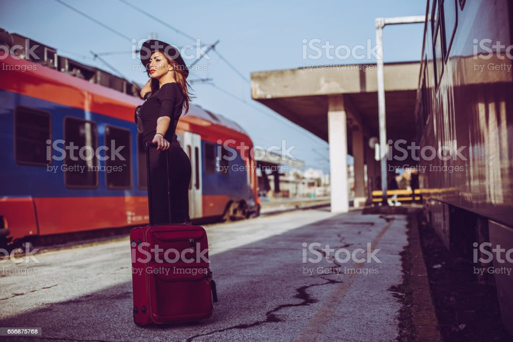 Gorgeous girl carrying the luggage at the train station stock photo