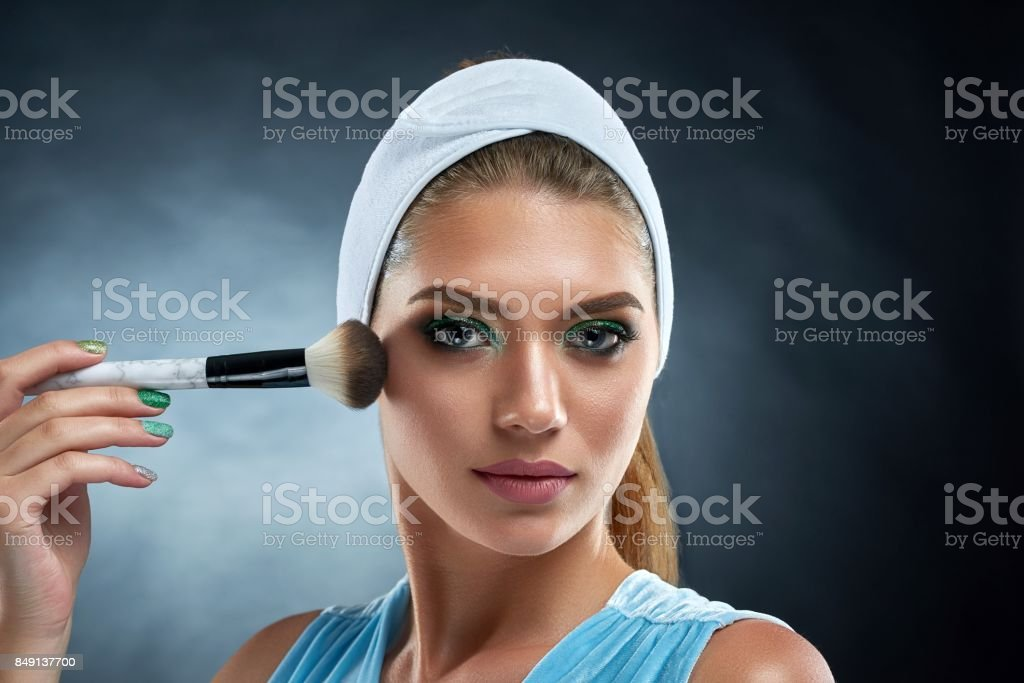 Gorgeous girl drawing blush for herself and posing at camera. stock photo