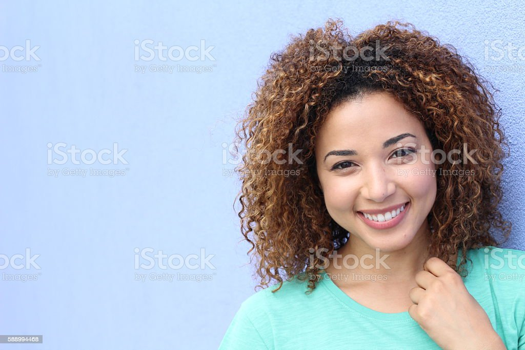 Gorgeous Hispanic woman touching her curly hair stock photo