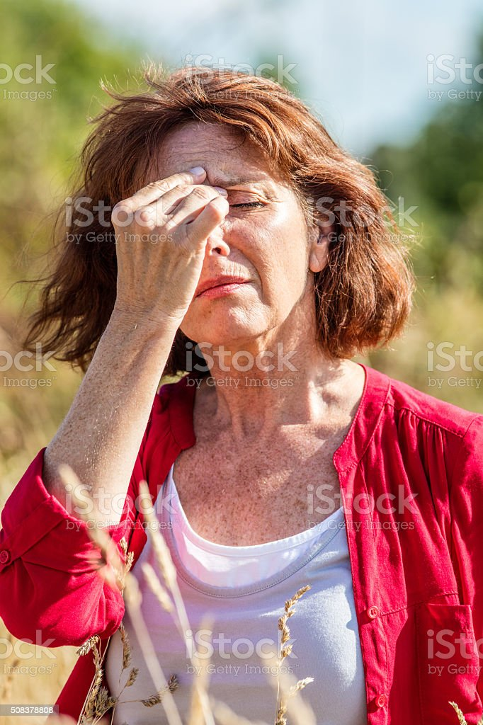 gorgeous mature woman with freckles suffering from hot flashes outdoors stock photo