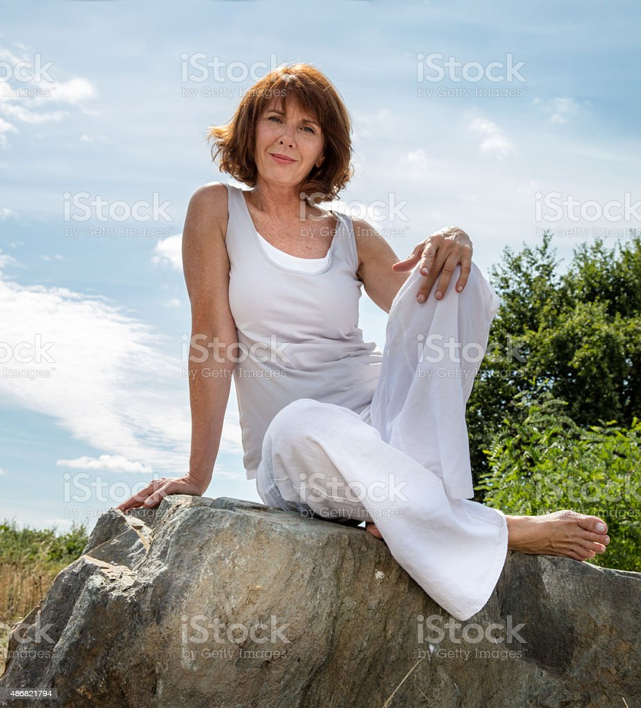 gorgeous mature yoga woman relaxing outdoors stock photo