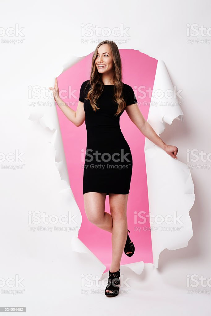 Gorgeous model emerging from torn paper, smiling stock photo