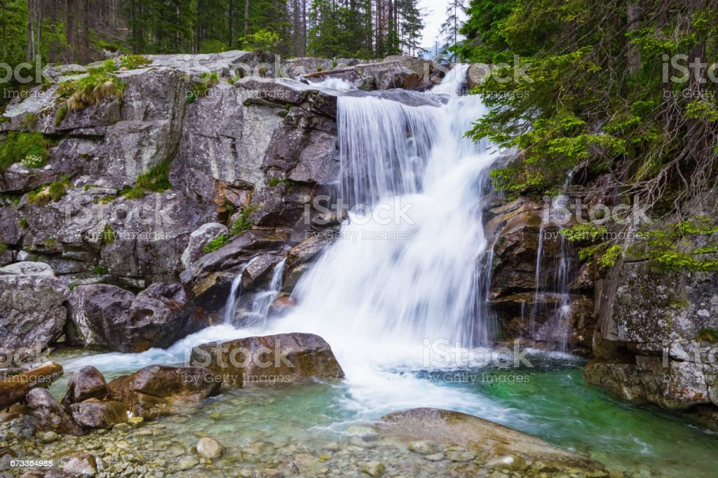 A gorgeous mountain waterfall flows among green forest and runs down the beautiful gray stones. A fascinating view. stock photo