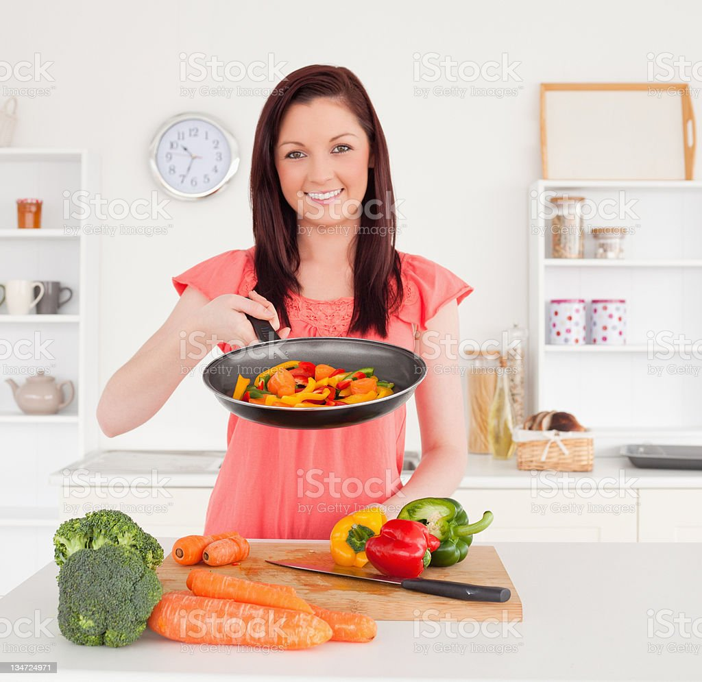 Gorgeous red-haired woman cooking vegetables in the kitchen stock photo