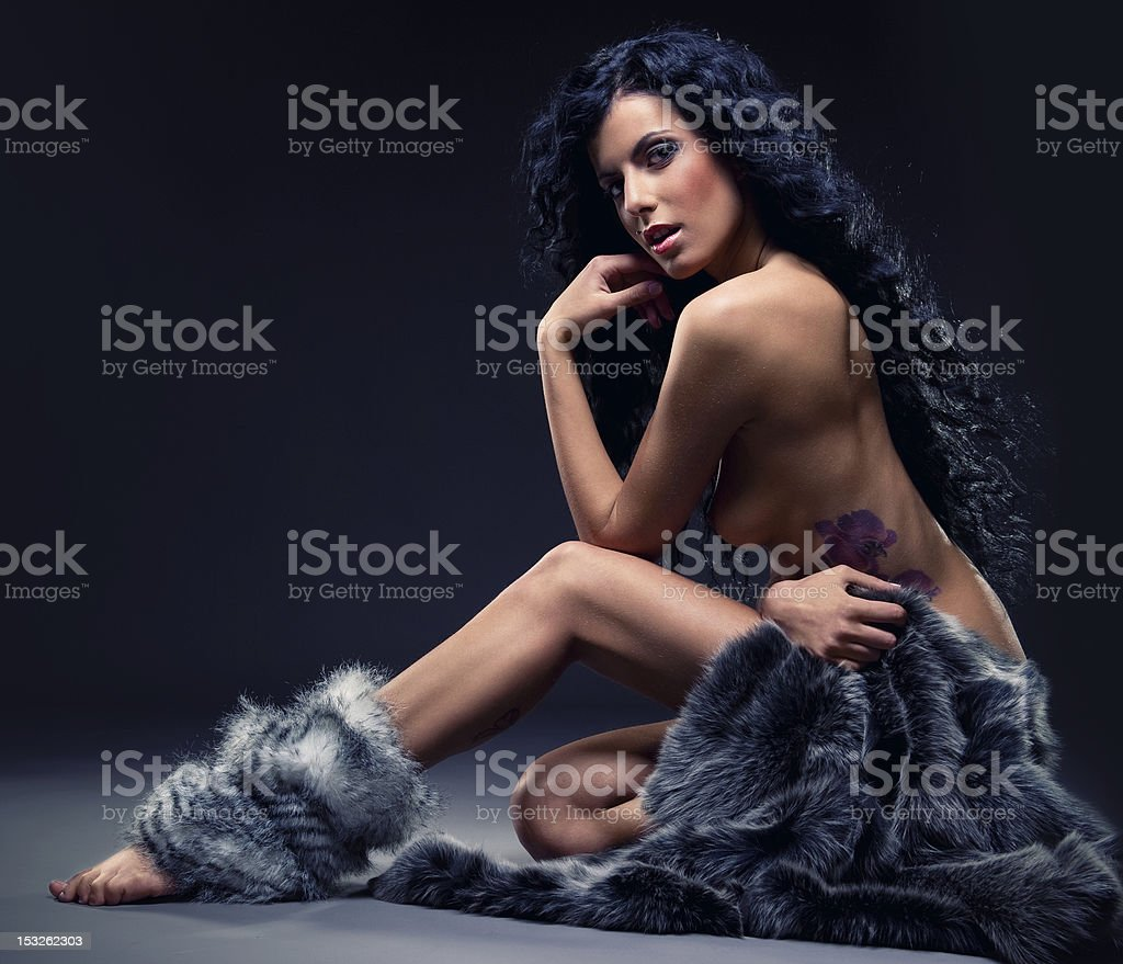 Gorgeous sexy brunette in fur posing indoors royalty-free stock photo