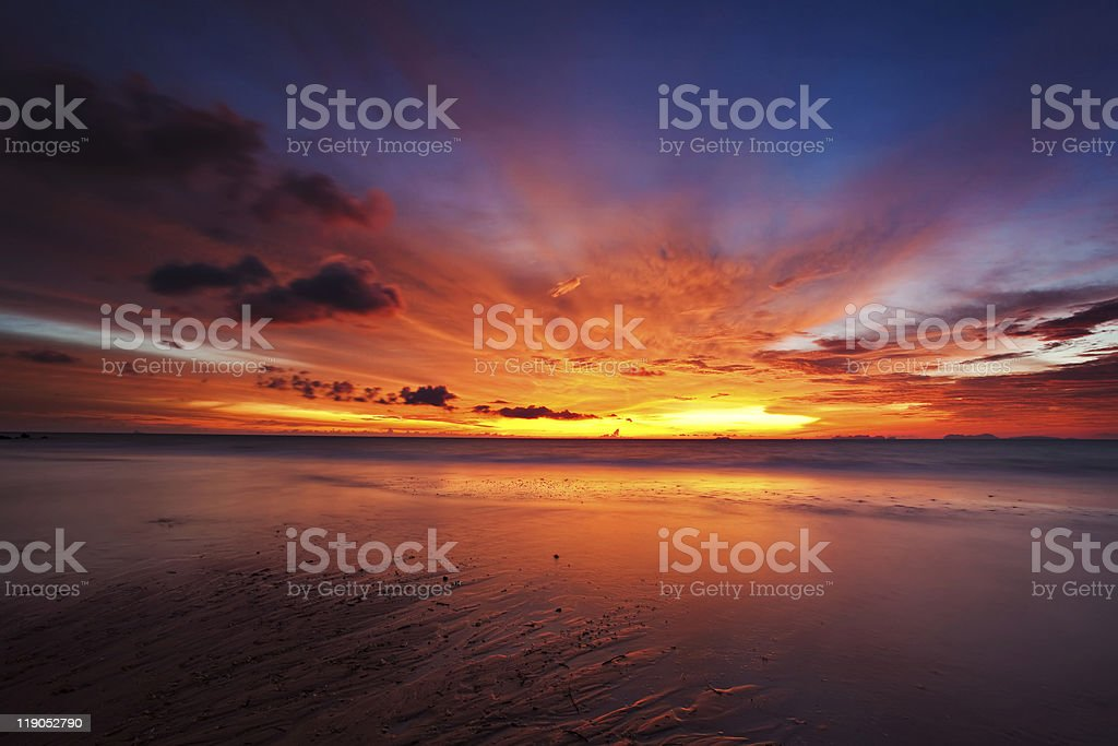 A gorgeous tropical sunset reflected on the beach royalty-free stock photo