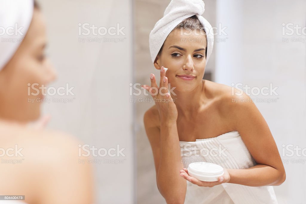 Gorgeous woman applying moisturizer on face stock photo