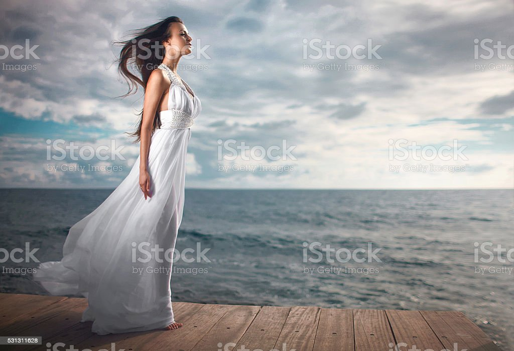 Gorgeous woman in white dress standing at pier. stock photo