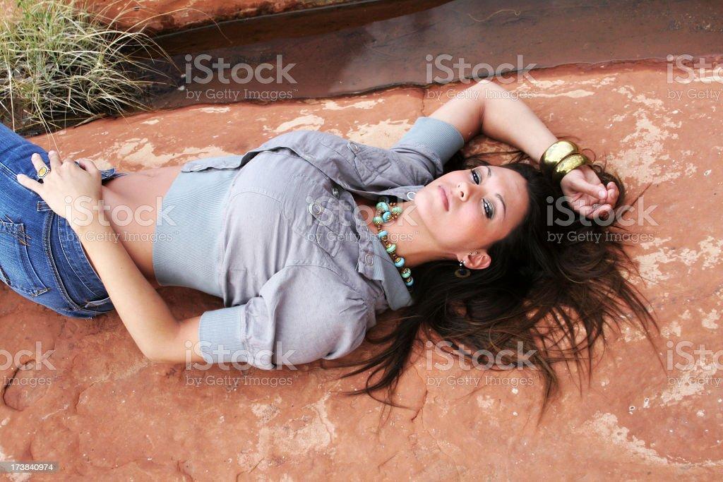 Gorgeous woman resting on a rock in Sedona Arizona stock photo
