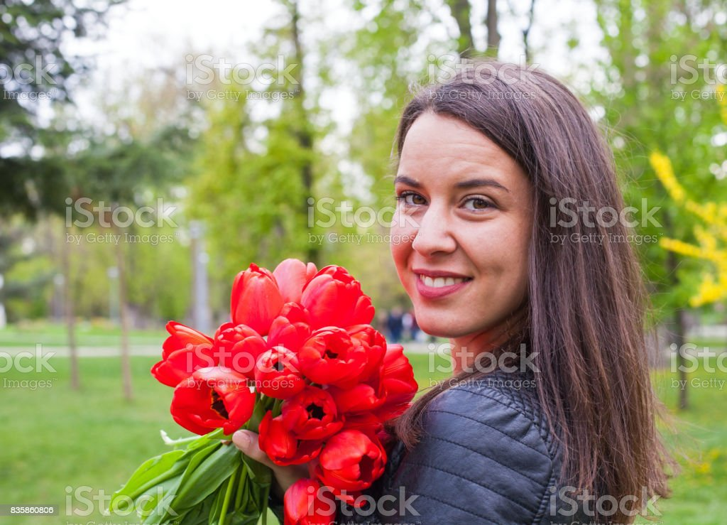Gorgeous woman with red tulips in the park stock photo