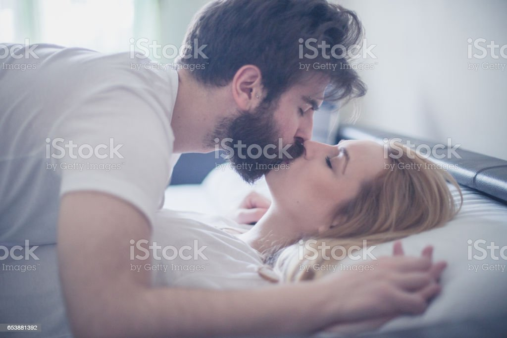 Gorgeous young couple kissing in the bed in the morning stock photo