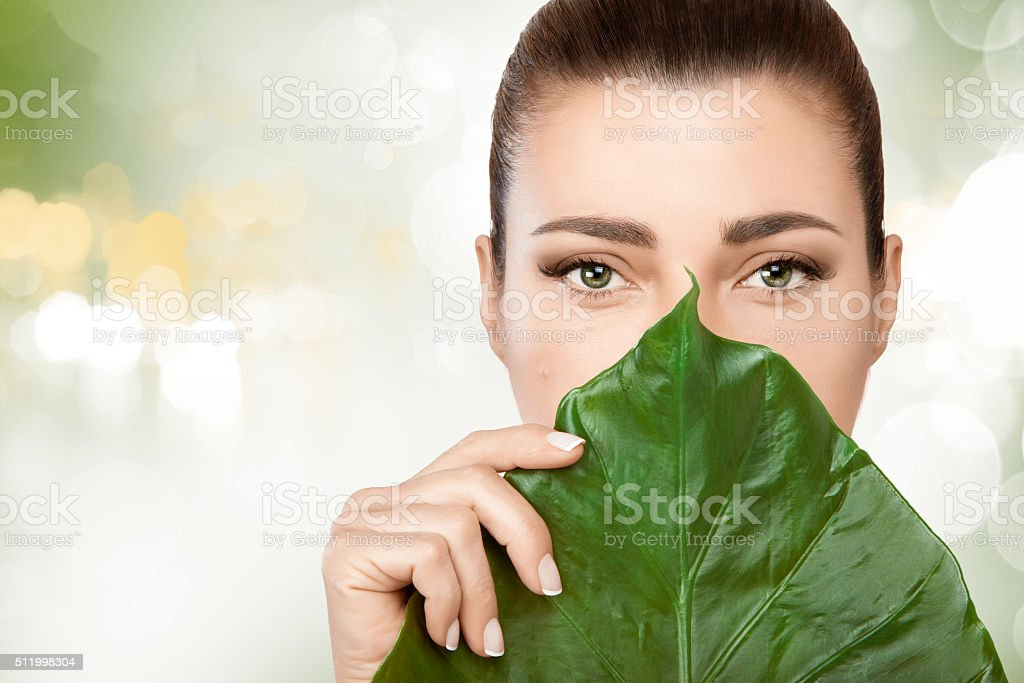 Gorgeous young woman with a fresh leaf to her face stock photo