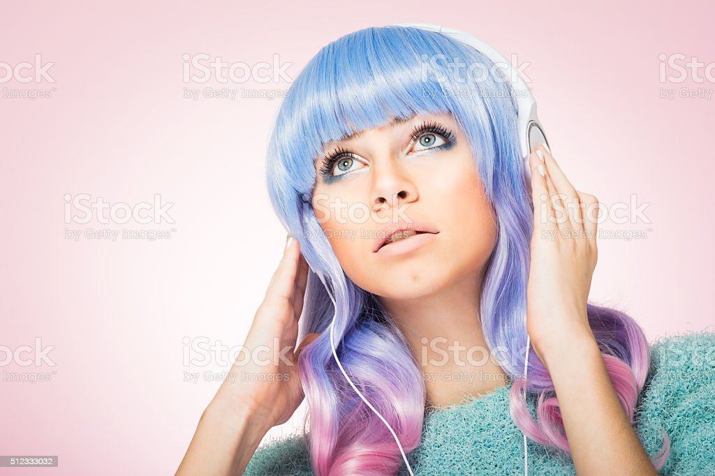 Gorgeous young woman with blue and pink hair and headphones stock photo