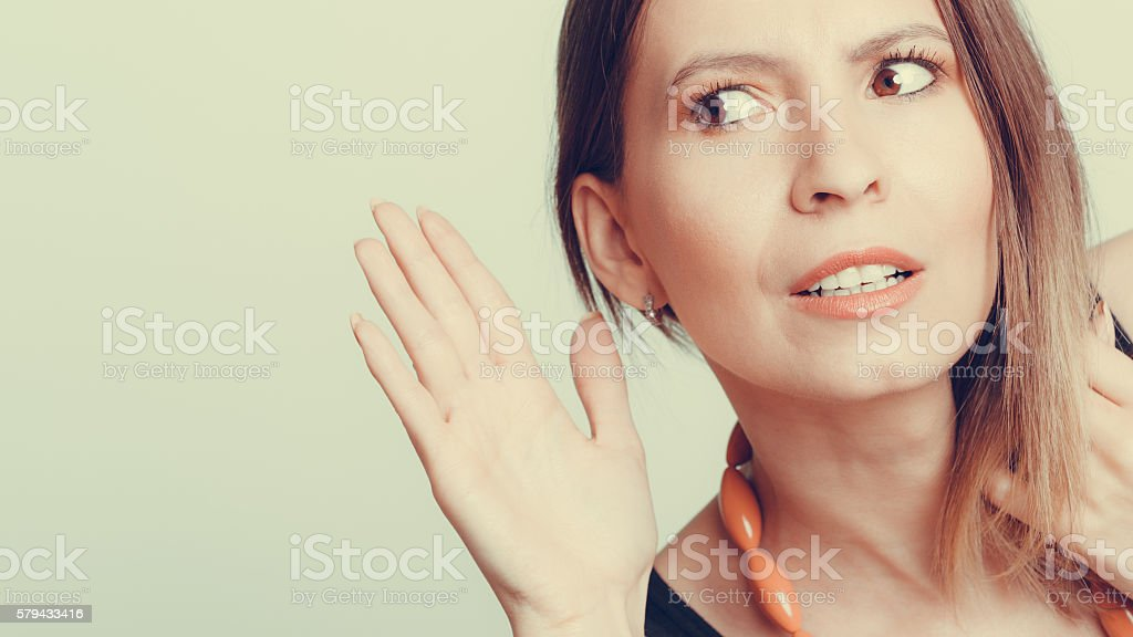 Gossip girl eavesdropping with hand to ear. stock photo