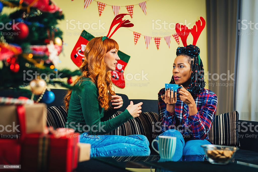 Gossip with my best friend at home for Christmas stock photo