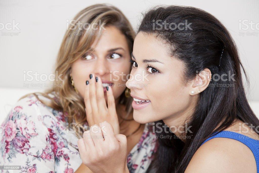 Gossiping: girlfriends telling secrets royalty-free stock photo