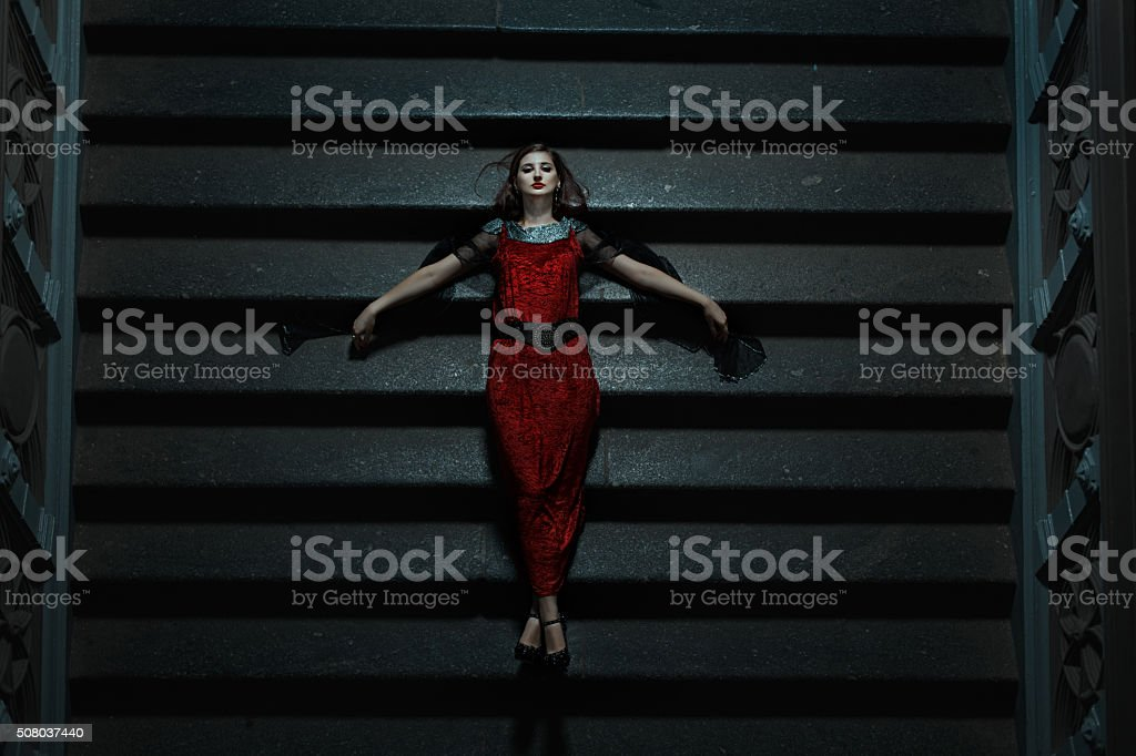 Gothic girl fell on the stairs at night. stock photo