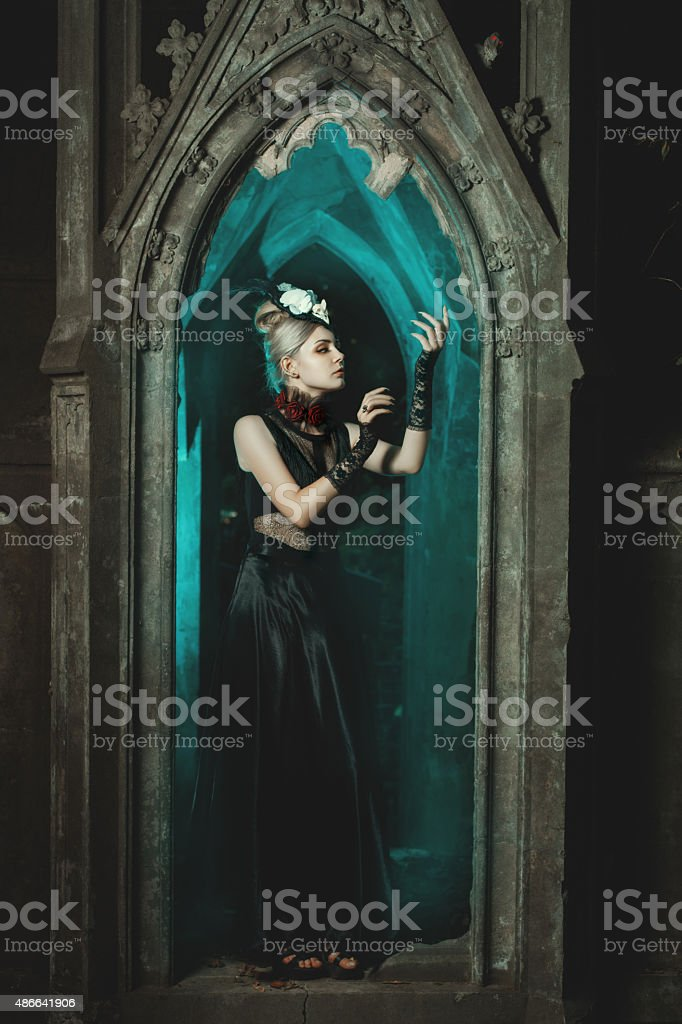 Gothic girl standing in the castle. stock photo