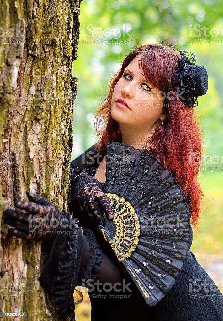 Fille gothique avec un fan dans le parc de printemps photo libre de droits