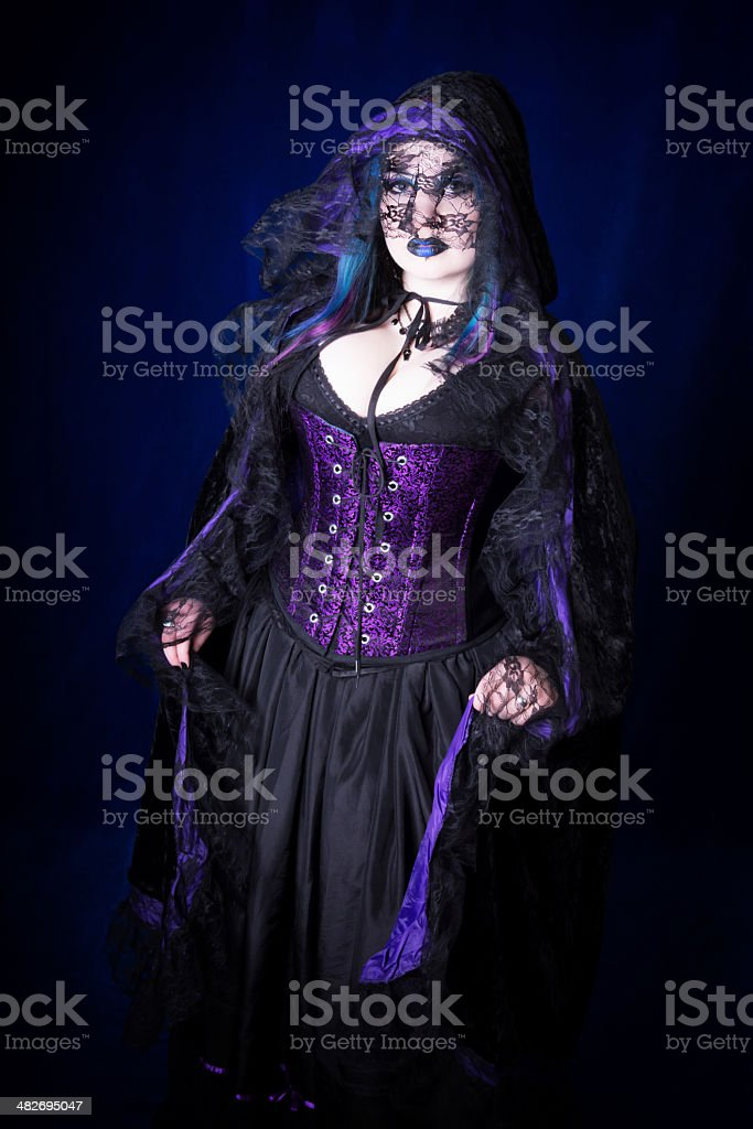 Gothic Vampire in lace cloak over corset and skirt. stock photo