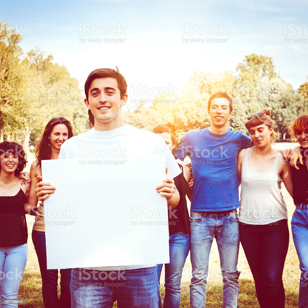 Goup of friends holding a billboard for copy space stock photo
