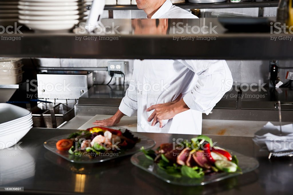 Gourmet appetizers, commercial kitchen, chef in background stock photo
