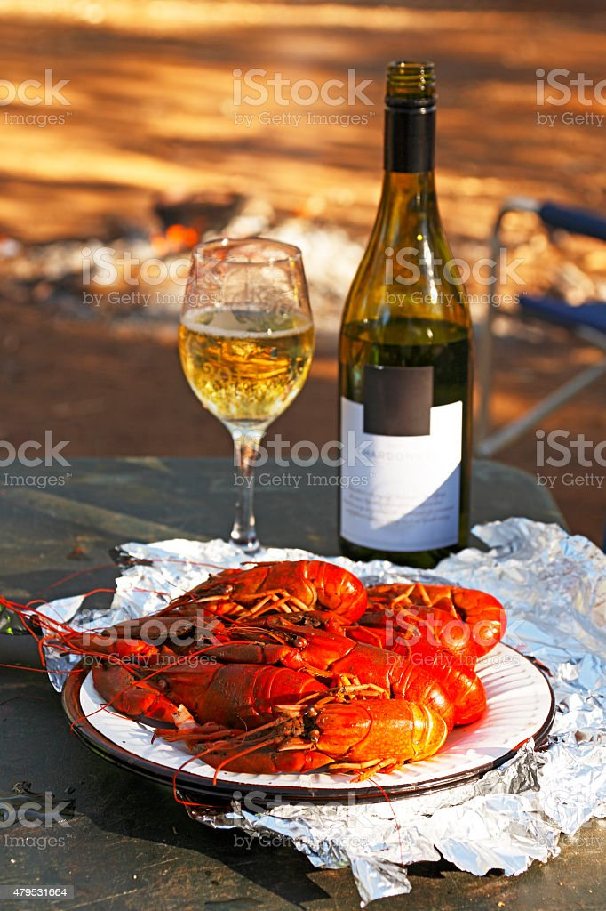 Gourmet camp breakfast of fresh cooked yabbies and white wine stock photo