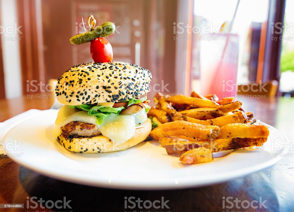Gourmet cheeseburger and French fries stock photo