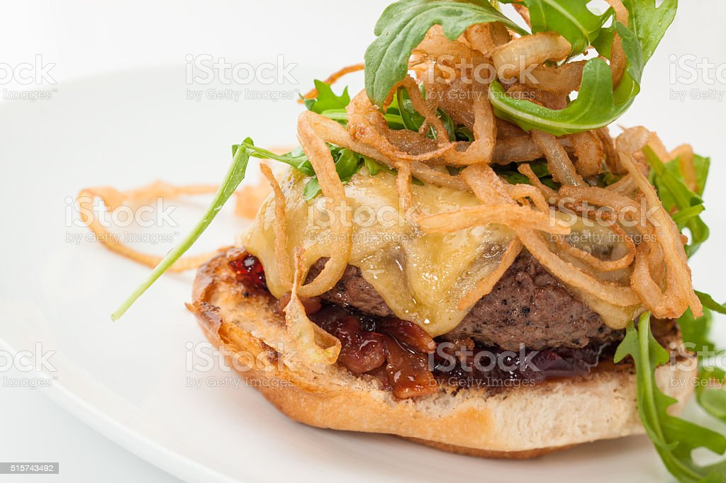 Gourmet cheeseburger with onion rings and arugula stock photo