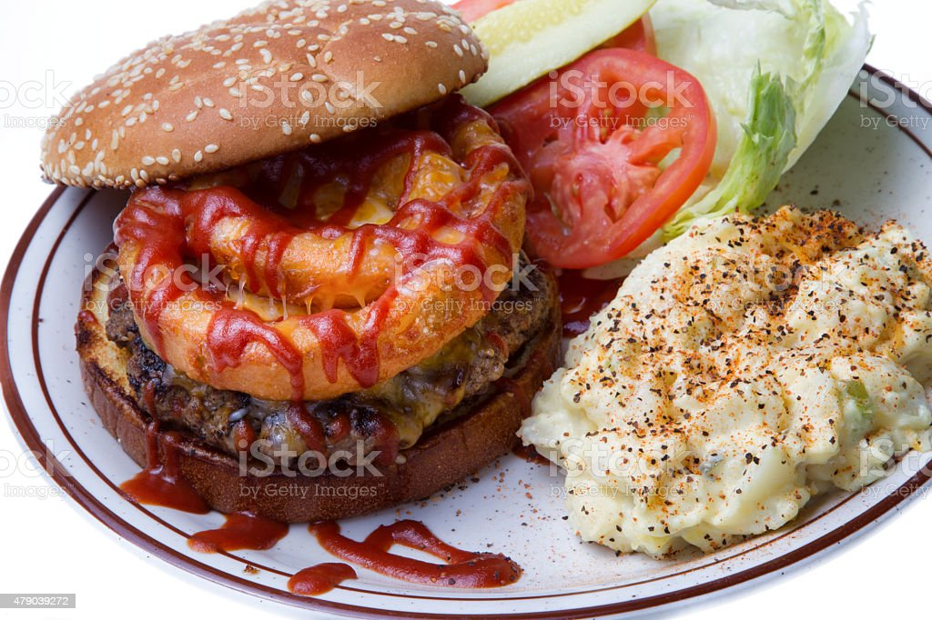 Gourmet Cheeseburger with Onion Rings and Potato Salad stock photo