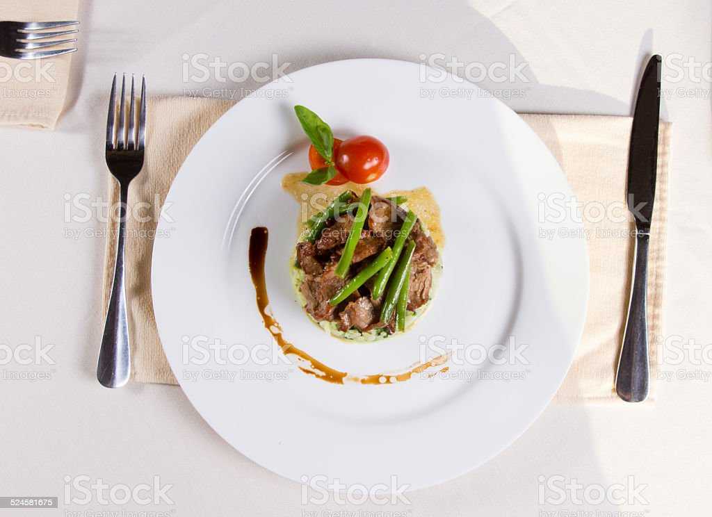 Gourmet Garnished Meaty Main Dish on Plate stock photo