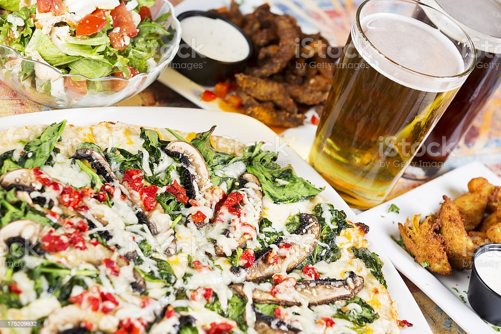 Gourmet pizza with beer, salad and appetizers stock photo